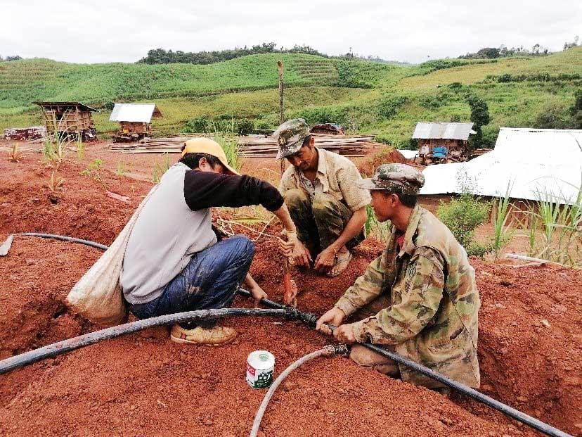 Three men working on improving irrigation